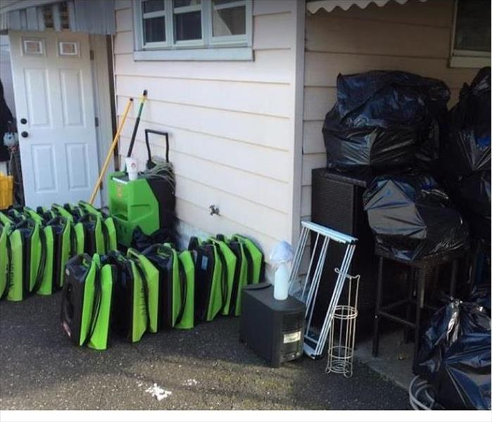 SERVPRO drying equipment stacked outside home after completing the restoration process