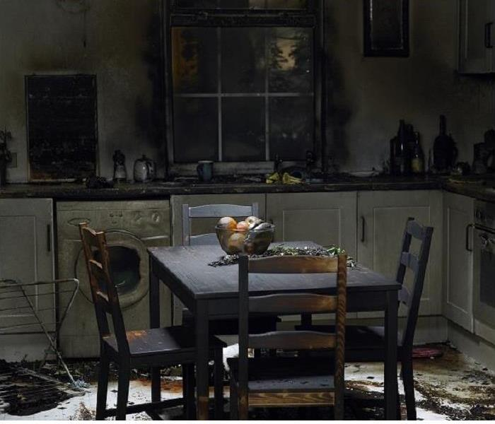 charred kitchen table and chairs in fire damaged kitchen