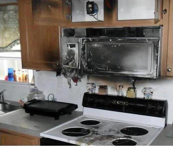 A stovetop covered in soot and smoke damage after a fire